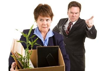 Fired corporate employee holding her belongings in a cardboard box, as her boss orders her out of the building.  Isolated on white.